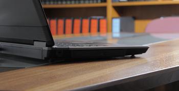 Notebook auf Tisch, im Hintergrund Bücherregal